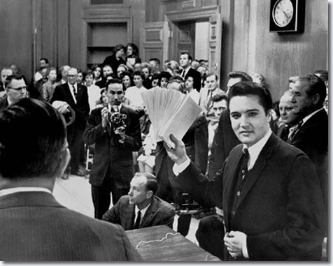 "More than 150 people jammed into the mayor's office Tuesday December 17, 1963 to see Elvis Presley hand out Christmas checks totaling $55,000. The checks benefitted 58 Memphis and Mid-South charities. In appreciation, the organizations presented Elvis with a six-foot plaque. It was warm in the room and when Commmissioner Claude Armour announced Elvis was going to pass out the checks, the singer wiped his brow and said, ""Elvis is going to pass out, period."""
